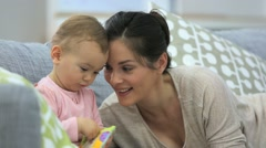 Mother and daughter reading book sitting in sofa Stock Footage