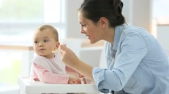 Baby girl eating in high chair, mommy by her side Stock Footage
