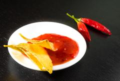 Crisp corn nachos with spicy hot tomato sauce as a snack or appetizer in a wh Stock Photos
