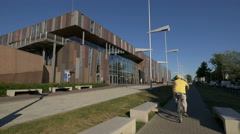 Riding a bike in front of the Copernicus Science Centre in Warsaw Stock Footage