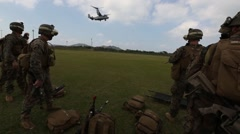 USMC Tilt-Rotor Osprey Lands in Background of Marines Standing - stock footage
