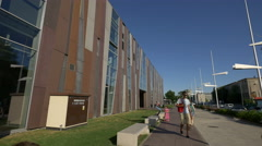 Walking and riding bikes next to Copernicus Science Centre Warsaw Stock Footage