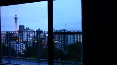 Widow with aerial urban view of Auckland city skyline at dusk Stock Footage