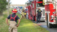 4K UHD - Emergency crews attending fire on road with traffic Stock Footage