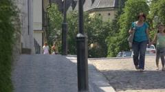 Women and little girl walking on a street in Prague Stock Footage