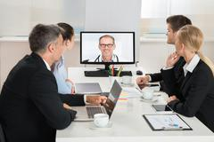 Team Of Businesspeople Videoconferencing With Doctors On Computer In Office Kuvituskuvat