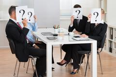 Group Of Businesspeople Hiding Faces Behind Question Mark Sign In Conference  - stock photo