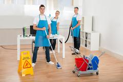 Cleaners Team In Uniform Cleaning Wooden Floor In Office - stock photo
