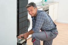Full length of mature handyman repairing refrigerator at home Stock Photos