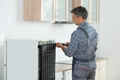 Cropped image of serviceman working on fridge with screwdriver at home Stock Photos
