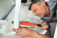 Cropped image of serviceman fixing sink pipe with adjustable wrench in kitche Stock Photos