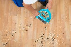 High angle view of male janitor sweeping floor with brush and dustpan - stock photo