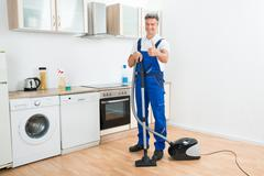 Full length portrait of male janitor cleaning floor with vacuum cleaner in ki Stock Photos