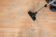 Low section of male janitor cleaning floor with vacuum cleaner in living room - stock photo