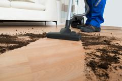 Low section of male worker cleaning floor with vacuum cleaner in living room - stock photo