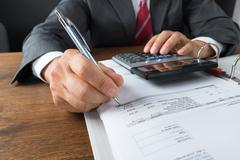 Mature businessman checking receipts with calculator at desk - stock photo