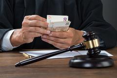 Male corrupt judge counting money at table in courtroom Kuvituskuvat