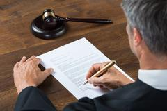 Rear view of judge writing on paper at table in courtroom Stock Photos