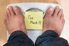 Low section of man standing on weight scale with too much sign Stock Photos