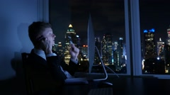 young caucasian businessman working in modern office. city skyline background - stock footage