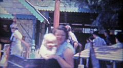 1962: Mom and baby enjoying dizzy hanging amusement park spinning ride at Knotts - stock footage
