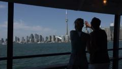 Two people enjoy ferry boat ride with Toronto skyline in background Stock Footage