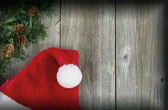 Santa cap and evergreen branch with vignette border on wooden boards - stock photo