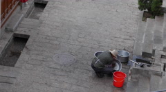 Chinese Man Cleaning His Pans On The Street In Lijiang China Stock Footage