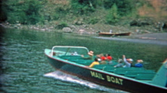 1957: Mail boat taking tourists up river sightseeing and dropping postage along Stock Footage