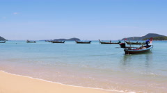 Long tail Fishing Boats in a bay with waves on shore Stock Footage