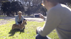 Multiethnic Man Takes Photos Of His Partner And Their Pet Corgi Dog In The Park Stock Footage
