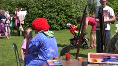 clown paint with colors on girl face in green park . 4K - stock footage