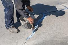 Worker apply layer of bonding adhesive - stock photo