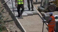 Stock Video Footage of Skilled builders brigade lay tiles sidewalk pavement. 4K
