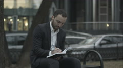 Young bearded business man thinking and wrighting notes at green park, traffic Stock Footage