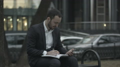 Young business man  working with papers and phone at green park, waiting for Stock Footage