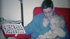 1964: Dad showing child box of chocolates in comfortable morning robe fashion. Stock Footage