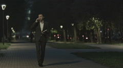 Businessman talking by phone while walking in park and use organizer Stock Footage