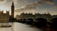 Boat passes under Westminster Bridge at sunset Stock Footage