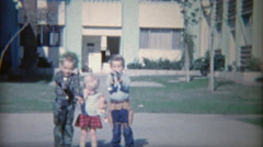 1964: Armed children with toy guns holstered shooting and laughing. Stock Footage