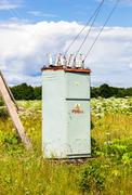 Voltage power transformer substation at the village in summertime Stock Photos