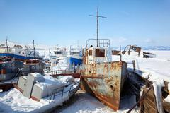 Old frozen ships in the port of Olkhon island on siberian lake Baikal - stock photo