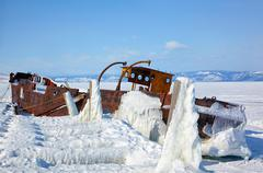 Old frozen ship on the bank of Olkhon island on siberian lake Baikal at winte - stock photo