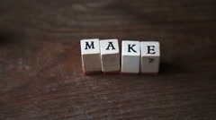 "Stop motion of an optimistic sentence ""make it real"" with alphabet stamp, indoor Stock Footage"