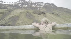 Model Enjoys Beautiful Mountainous Icelandic Landscape from Geothermal Hotspring Stock Footage