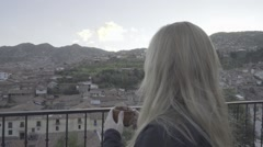 Model Smiles as she Enjoys a Hot Beverage Overlooking a Foreign Town Stock Footage