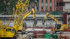 Excavators and cranes on the construction site under construction skyscraper. - stock footage