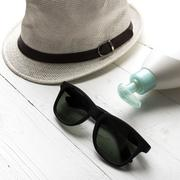 Hat sunglasses and body lotion Stock Photos