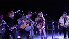 man play guitar and woman sing poetry at night. 4K - stock footage