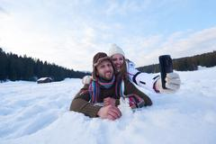 romantic couple have fun in fresh snow and taking selfie - stock photo